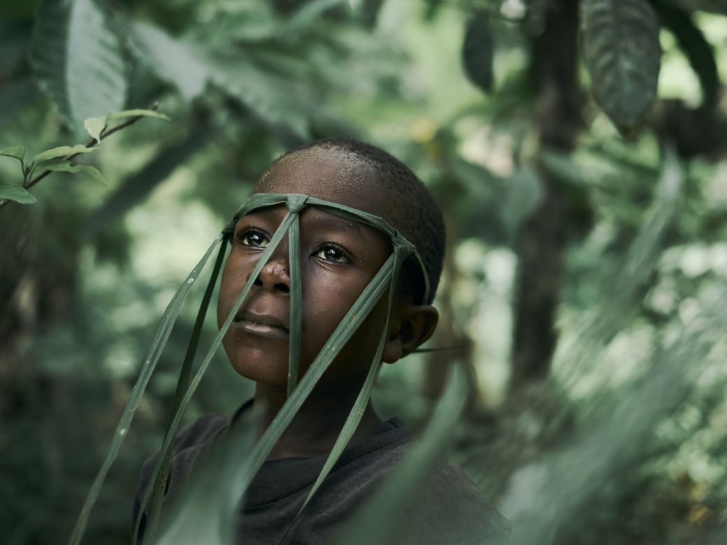 boy with leaves on his face
