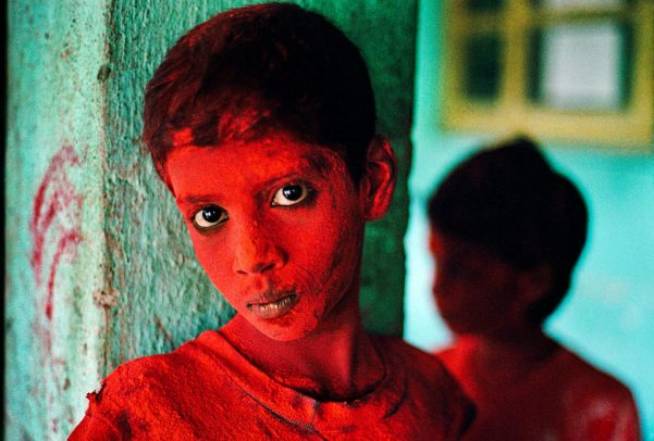 Boy covered in red powder