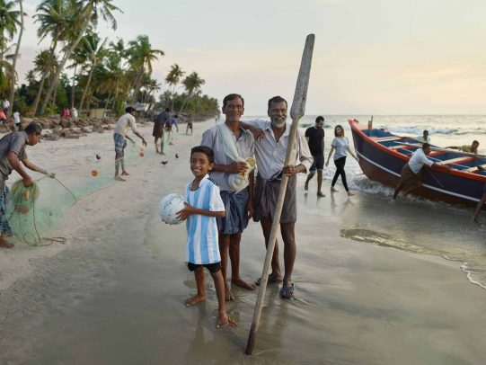 Two men and a child on the beach for Kerala Tourism Campaign by Joey L.