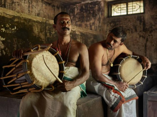 men without shirts playing drums