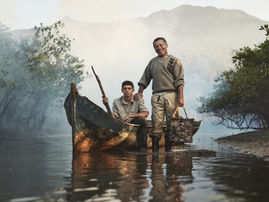 Father and son on a boat in a river for Lavazza Calendar 2016 by Joey L