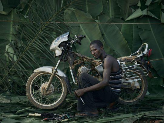 portrait of man repairing his motorcycle