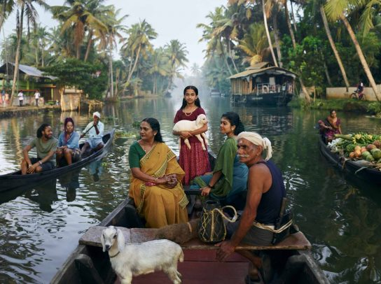 people on a boat on a river and a girl standing and holding a lamb for Kerala Tourism Campaign by Joey L.