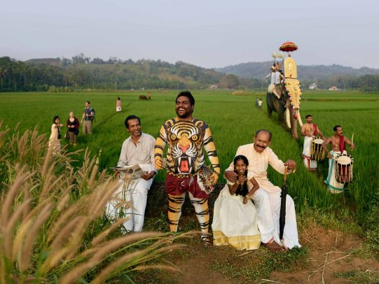 man painted with a tiger on his belly during a procession in field in Kerala for Kerala Tourism Campaign by Joey L.