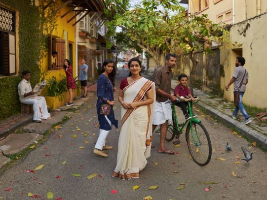Woman in a street and a man on a bicycle with his child for Kerala Tourism Campaign by Joey L.