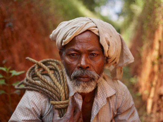 indian man with a white turban holding a rope on his shoulder