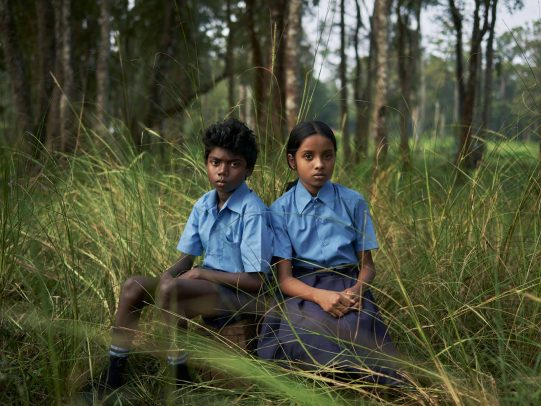 two indian children sitting in a forest