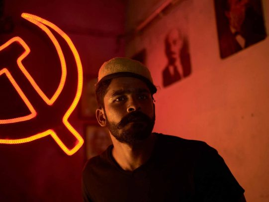 man with hat and hammer and sickle on the background