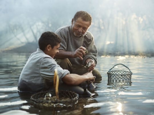 father and son working in a river for Lavazza Calendar 2016 by Joey L