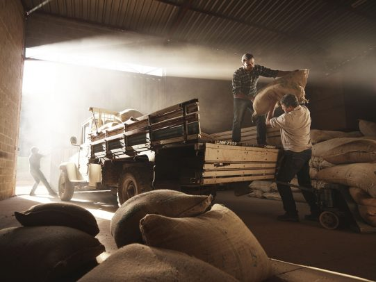 two men loading bags on a pickup for Lavazza Calendar 2016 by Joey L