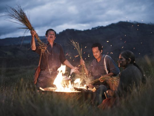 Men around fire and holding long blades of grass for Lavazza Calendar 2016 by Joey L