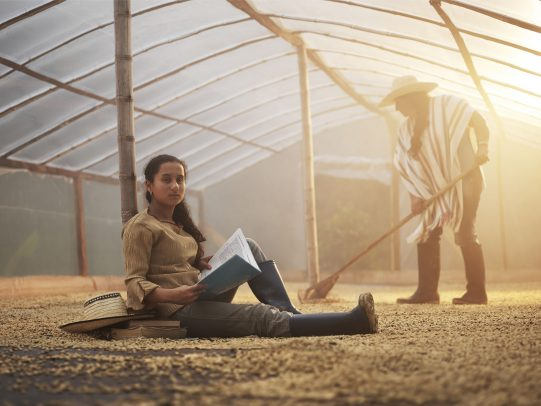 Girl studying in a coffee greenhouse while a man work in the background for Lavazza Calendar 2016 by Joey L