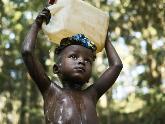 a child carries a jerry can with water on his head