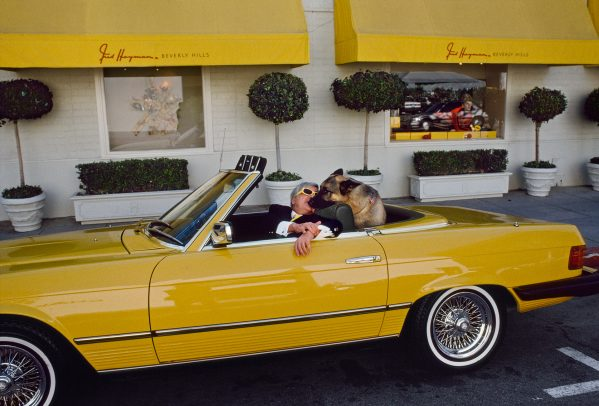 man with his dog in his yellow car
