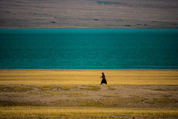 woman walking along a lake in Tibet
