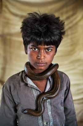 Boy with a snake around his neck