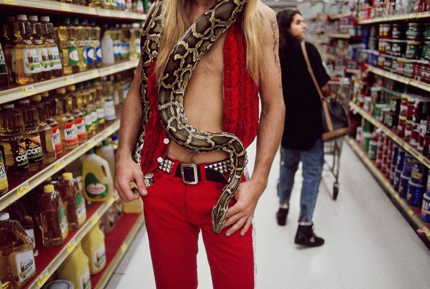 man with a snake around his neck in a supermarket
