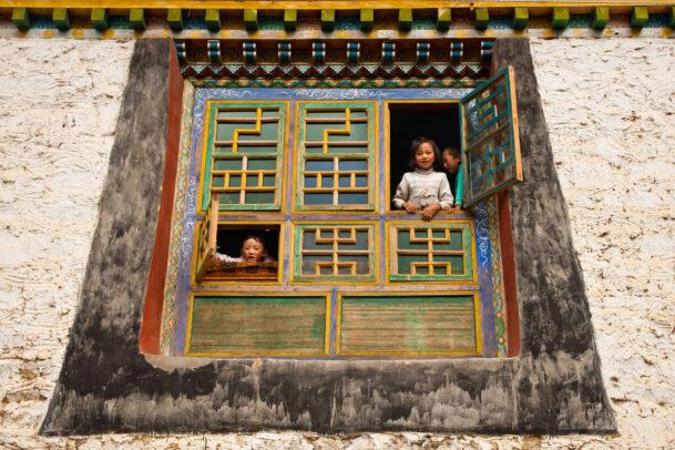 children at a window in Tibet