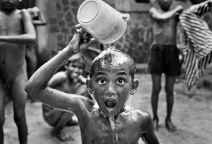 boy pouring some water on his head