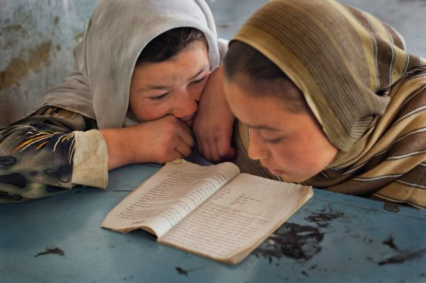 Two young girls read at school