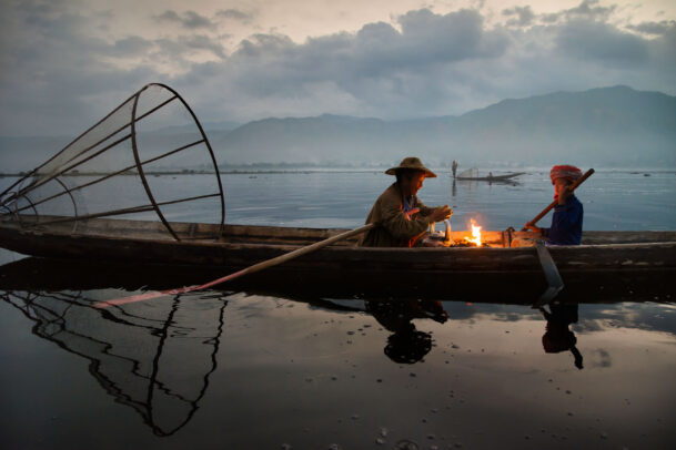 Two fisherman sit by a campfire in a canoe on the inle lake