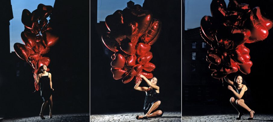 woman holding some red baloons in shape of heart