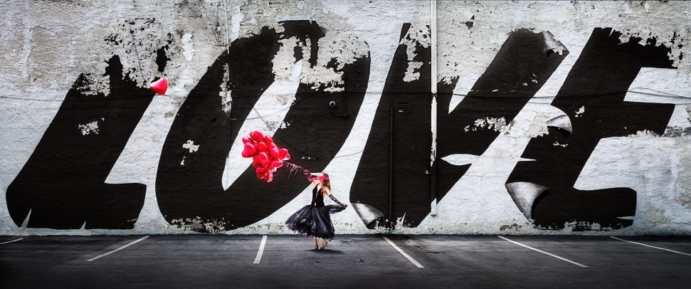 woman dancing holding some baloons in front a big graffiti