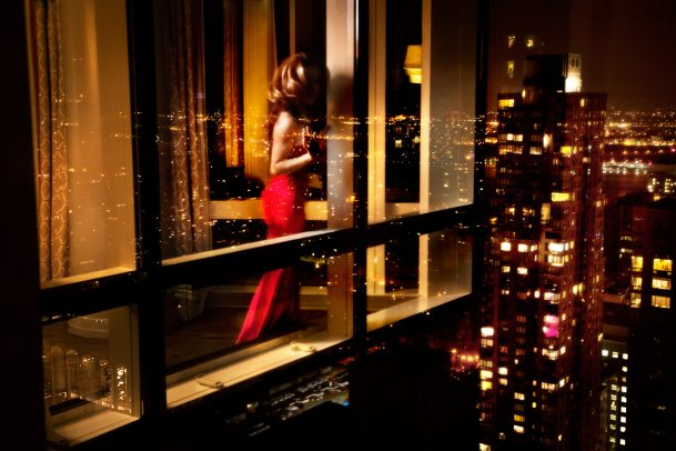 woman with red dress looking through window of a