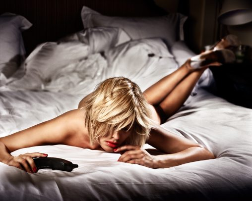 Naked woman on a bed with heels and holding a phone