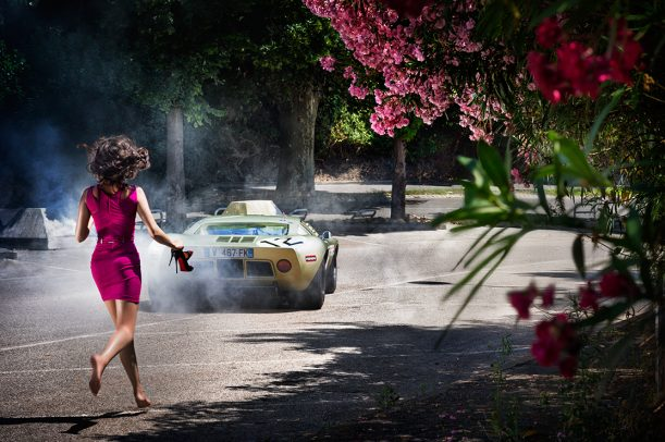woman running to a sport car holding her heels
