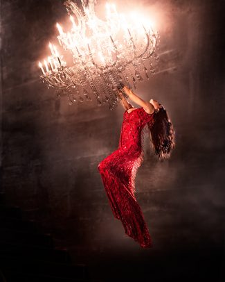 woman in red dress hung on a chandelier