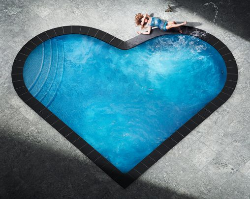 woman relaxing at a heart shaped pool