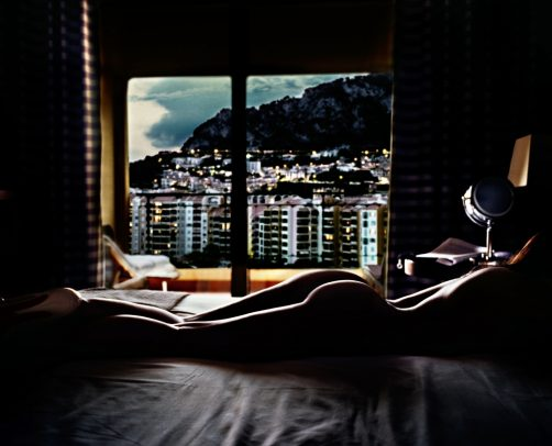 naked woman on the bed and a window with city landscape