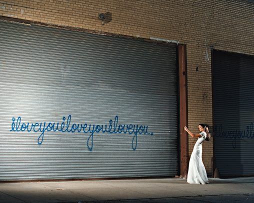 woman with white long dress taking picture of a graffiti on a