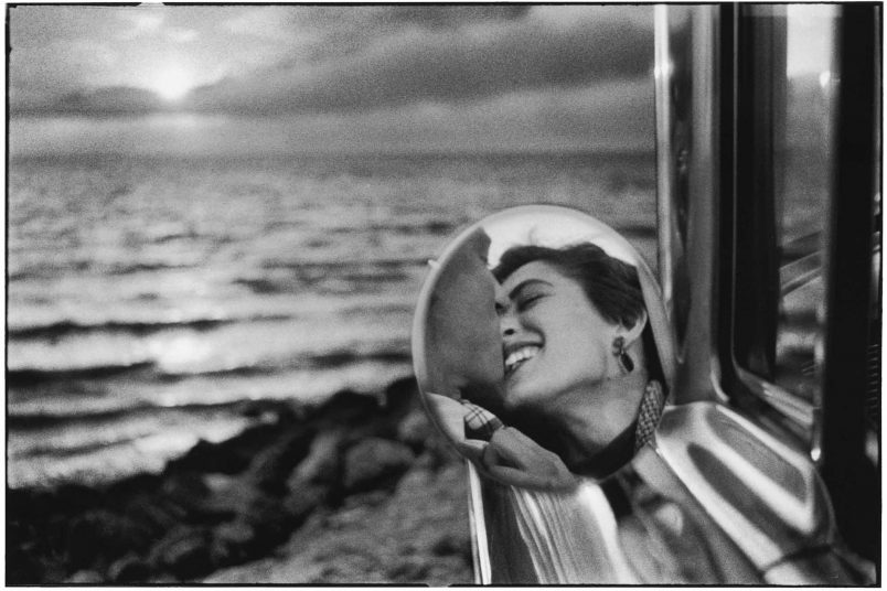a reflection in a rear view of a man and a woman kissing at the beach