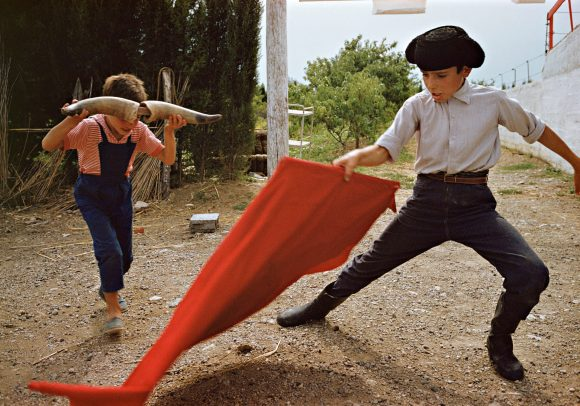 two children playing with horns of a pull and a red flag