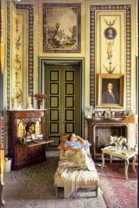 a woman lying on a couch in an ancient and rich room