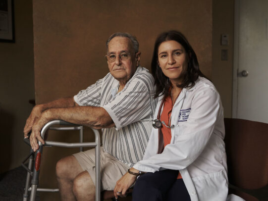 a doctor and her patient with his walker during Novartis annual report by Joey L.
