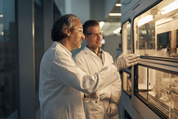 two doctors in front of a lab talking each other during Novartis annual report by Joey L.