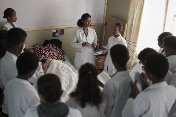 a doctor in hospital with her pupils and a patient in bed during Novartis annual report by Joey L.