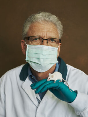 doctor with surgical mask and gloves, holding a guinea pig for Novartis annual report by Joey L.