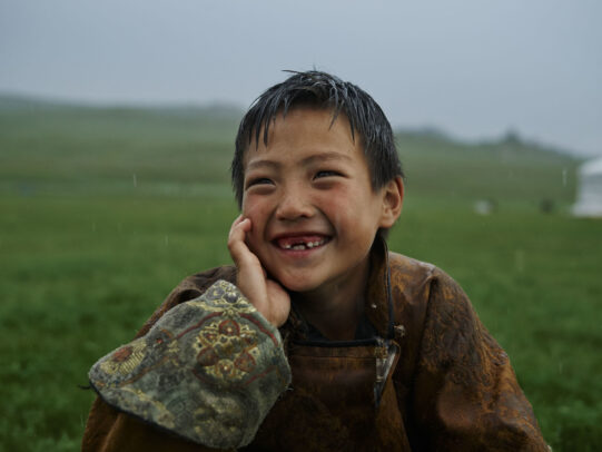 mongolian boy smiling under rain during Novartis annual report by Joey L.