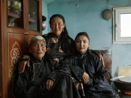 three mongolian people in a house