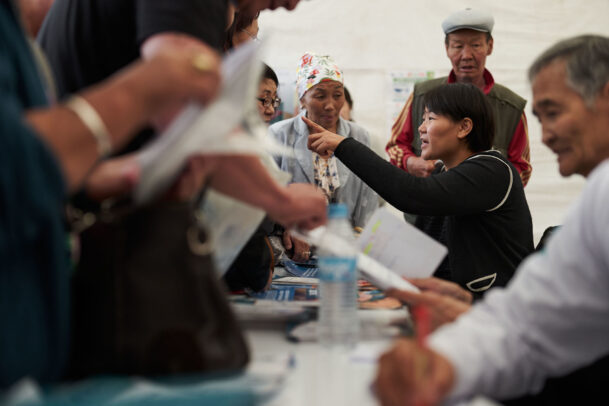 a mongolian woman indicating for a crowd of people during Novartis annual report by Joey L.