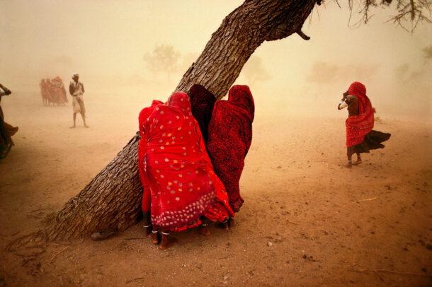 girls hiding in their saris and protecting from the dust storm