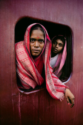 woman and child looking outside a window train in Calcutta