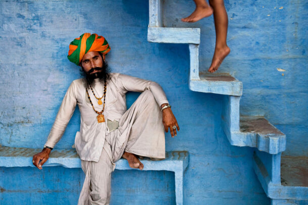 A man with orange and green turban sits beneath blue stairs