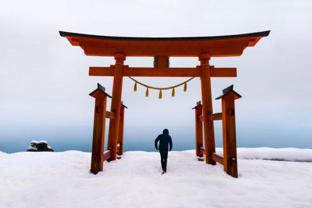 Man under japanese torii in gozanoishi Shrine