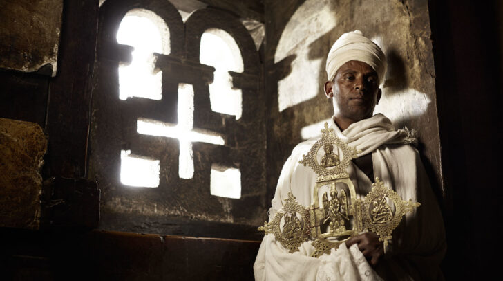 man wearing white robes and turban and holding a big golden cross near a crossed window