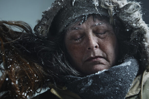 woman with hood and closed eyes in a blizzard
